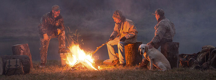 guys around campfire with dog wearing a garmin trashbreaker e collar